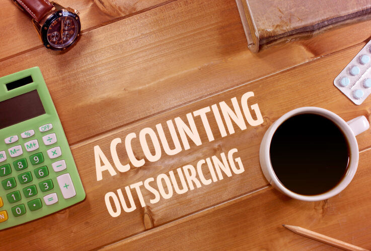 Green calculator lies on wooden desk with inscription Accounting outsourcing